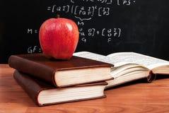 Roter Apfel auf Büchern und Schultafel mit mathematischen Gleichungen im Klassenzimmer Stockfoto
