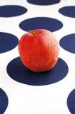 Roter Apfel auf blauem und weißem Tabellentuch Lizenzfreie Stockfotos
