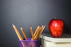Roter Apfel auf Buch mit Bleistift-und Tafel-Kreide-Brett Lizenzfreie Stockbilder