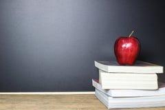 Roter Apfel auf Buch mit Tafel-Kreide-Brett als Hintergrund Lizenzfreie Stockfotografie