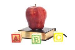 Roter Apfel auf Buch und ABCs hölzernen Buchstabe-Blöcken Stockfoto