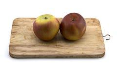 Roter Apfel auf dem Hacken des Holzes lokalisiert auf weißem Hintergrund Lizenzfreie Stockbilder