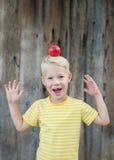 Roter Apfel auf dem Kopf eines Kindes Stockbild