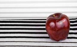 Roter Apfel auf dem stripey Hintergrund lizenzfreies stockfoto