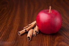 Roter Apfel auf dunkler hölzerner Tabelle mit Steuerknüppeln des Zimts Lizenzfreie Stockfotografie