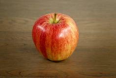 Roter Apfel auf einem hölzernen Substrat Stockfotografie