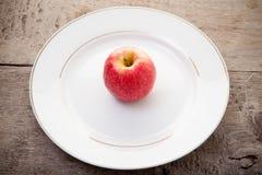 Roter Apfel auf einem weißen Teller Lizenzfreie Stockfotos