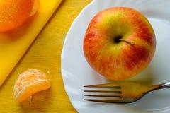 Roter Apfel auf einer Platte mit Gabel und Mandarine Lizenzfreie Stockbilder