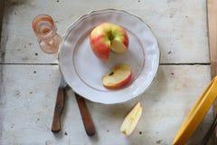 Roter Apfel auf einer Platte und einem Wodka in einem transparenten Weinglas Lizenzfreie Stockfotografie