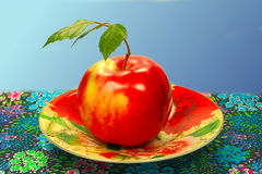 Roter Apfel auf einer Untertasse Lizenzfreie Stockfotos