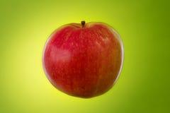 Roter Apfel auf grünem Hintergrund Stockbild