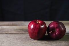 Roter Apfel auf hölzerner Tabelle auf dunklem Hintergrund Lizenzfreie Stockfotos