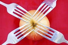 Roter Apfel auf Rot mit vier Gabeln Lizenzfreie Stockbilder