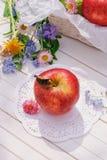 Roter Apfel auf weißer Gartentabelle Stockfotografie