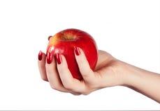 Roter Apfel in der Hand auf einem weißen Hintergrund Lizenzfreies Stockfoto