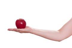 Roter Apfel der Versuchung in einer weiblichen Hand Lizenzfreie Stockfotos