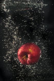 Roter Apfel, der in Wasser fällt Lizenzfreie Stockfotografie