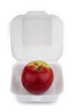 Roter Apfel in einer Schnellimbissverpackung auf weißem Hintergrund Lizenzfreies Stockfoto
