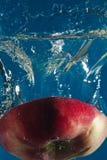Roter Apfel geschnitten zur Hälfte im Wasser lizenzfreie stockfotos
