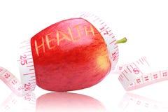 Roter Apfel, Gesundheitstext und messendes Band herum eingewickelt. Stockfotografie