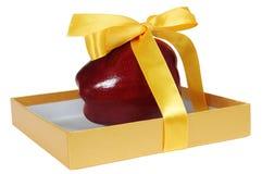 Roter Apfel im Kasten mit gelbem Band wie Geschenk Stockfoto
