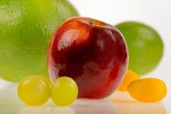 Roter Apfel mit anderen Früchten auf einem weißen Hintergrund, intensiv bunt und rund lizenzfreie stockfotos