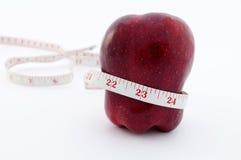 Roter Apfel mit Bandmaß um Taille Stockfotografie