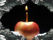 Roter Apfel mit brennender Kerze Lizenzfreie Stockbilder