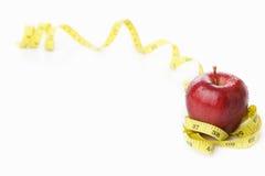 Roter Apfel mit messendem Band Stockbilder