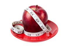 Roter Apfel mit messendem Band auf roter Platte Stockfotografie