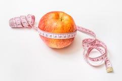 Roter Apfel mit messendem Band - nähren Sie Konzept Stockfotografie