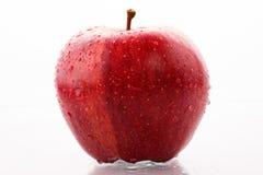Roter Apfel mit Tropfen des Wassers Stockbild