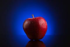 Roter Apfel mit Wasser fällt auf blauen Hintergrund Lizenzfreie Stockfotografie