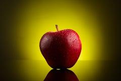 Roter Apfel mit Wasser fällt auf gelben Hintergrund Stockbilder