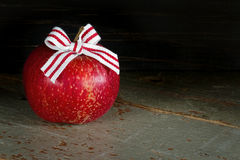 Roter Apfel mit Weihnachtsbogen auf dunklem Hintergrund Stockbilder
