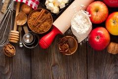 Roter Apfel, Nelken und Zimtsteuerknüppel auf einem Ausschnittvorstand Stockfotografie