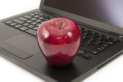 Rotes Apple auf einem Laptop lizenzfreies stockbild