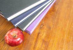 Roter Apfel und alte Bücher auf hölzerner Tischplatte Lizenzfreie Stockfotos