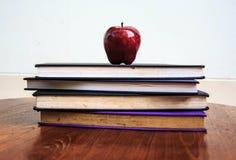Roter Apfel und alte Bücher auf Holztisch Stockfoto