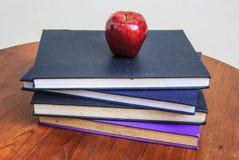 Roter Apfel und alte Bücher auf Holztisch Lizenzfreies Stockbild