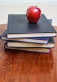 Roter Apfel und alte Bücher auf Holztisch Stockbilder