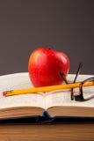 Roter Apfel und Buch Stockfoto