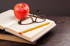 Roter Apfel und Buch Stockfotos