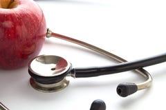 Roter Apfel und ein medizinisches Stethoskop auf einer Tabelle Stockbilder