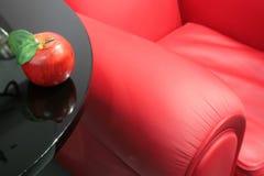 Roter Apfel und ein roter Sessel Lizenzfreie Stockfotografie