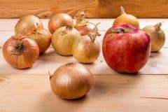 Roter Apfel und einige Zwiebeln stockfotografie