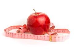 Roter Apfel und messendes Band auf einem weißen Hintergrund Stockbilder