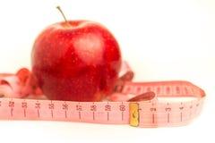 Roter Apfel und messendes Band auf einem weißen Hintergrund Lizenzfreie Stockbilder