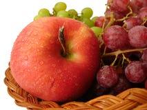 Roter Apfel und Trauben im Korb auf weißem Hintergrund Lizenzfreies Stockfoto