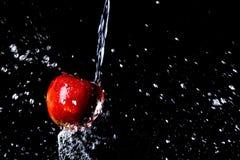 Roter Apfel unter dem Spritzen auf einem schwarzen Hintergrund Stockbilder